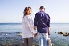 Lyckligt paranseende på en havspir Stilfulla par som rymmer handen, lockigt hår, vit skjorta, orsaklig dräkt, par som vilar, lopp Fotografering för Bildbyråer
