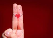 Lyckligt parbegrepp. Två fingrar som är förälskade med målat leende Arkivbild