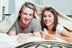 Lyckligt parnederlag under deras filt Royaltyfri Bild