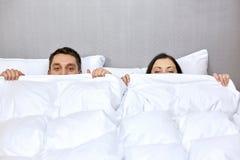 Lyckligt parnederlag under filten i säng Royaltyfri Foto