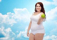 Lyckligt plus formatkvinna i underkläder med äpplet Royaltyfria Foton
