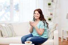 Lyckligt plus formatkvinna med koppen och kakor hemma arkivfoton
