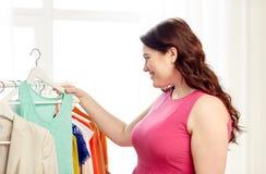 Lyckligt plus formatkvinnan som väljer kläder på garderoben Arkivbilder