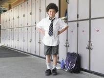 Lyckligt pojkeanseende vid skolaskåp royaltyfria foton