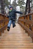 Lyckligt pojkehoppa och spring på en träbro i skogen royaltyfria bilder