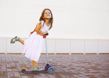 Lyckligt positivt barn i klänning på sparkcykeln i staden Arkivbild