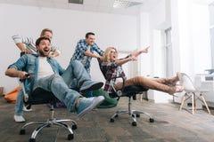 Lyckligt positivt folk som rider i svängtappstolarna arkivfoton