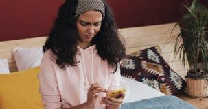 Lyckligt prata för afrikansk amerikanflicka och textmessaging på smartphonen som hemma sitter på sängen Den unga kvinnan mottar lager videofilmer