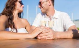 Lyckligt precis gift par med champagne på kafét Royaltyfri Foto