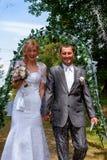 Lyckligt precis gift par under ett risregn Royaltyfri Foto