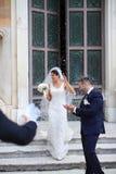 Lyckligt precis gift par under ett risregn royaltyfri fotografi