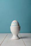 Lyckligt påskmeddelande på ägget i äggkopp Arkivfoto