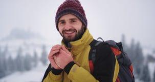 Lyckligt resa för karismatisk ung turist- stående i mitt av berget som han ser till kameran har röda kalla händer stock video