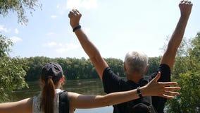 Lyckligt resorbegrepp Man- och flickavandring tillsammans Fotvandrare med ryggsäckar stoppar på flodbanken och ser ut på den dem stock video
