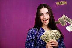 Lyckligt rikt kvinnaanseende under dusch fr?n pengar royaltyfri bild