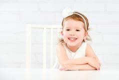Lyckligt roligt roligt flickabarn som skrattar på den tomma vita tabellen Royaltyfria Foton