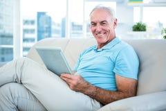 Lyckligt sammanträde för hög man på soffan med den digitala minnestavlan Fotografering för Bildbyråer