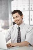 Lyckligt sammanträde för kontorsarbetare på skrivbordet genom att använda bärbara datorn royaltyfri fotografi