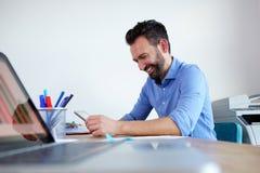 Lyckligt sammanträde för man för mogen affär på hans skrivbord och använda den digitala minnestavlan Fotografering för Bildbyråer