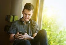Lyckligt sammanträde för tonårs- pojke på fönster och användatelefonen Royaltyfri Fotografi