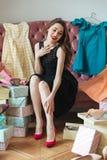 Lyckligt sammanträde för ung dam på soffan som väljer inomhus skor Royaltyfri Fotografi