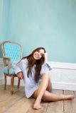 Lyckligt sammanträde för ung kvinna på det wood golvet och koppla av hemma Royaltyfri Fotografi