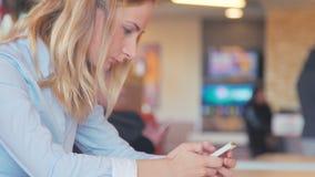 Lyckligt sammanträde för ung kvinna på en tabell med ett kaffe genom att använda mobiltelefonen lager videofilmer
