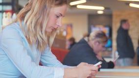 Lyckligt sammanträde för ung kvinna på en tabell med ett kaffe genom att använda mobiltelefonen stock video
