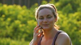 Lyckligt sammanträde för ung kvinna på grön gräsmatta och samtal på telefonen eller smartphonen arkivfilmer