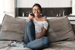 Lyckligt sammanträde för ung kvinna på hemmastadd klockaTV för soffa arkivbilder