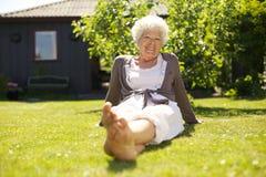 Lyckligt sammanträde för äldre kvinna som kopplas av i trädgård Arkivbild