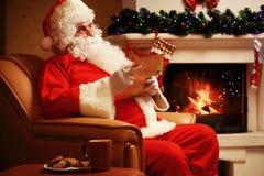 Lyckligt Santa Claus sammanträde på hans hemmastadda near julgran för rum och stora läs- julbrev för säck och eller önskelista Royaltyfria Bilder