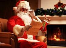 Lyckligt Santa Claus sammanträde på hans hemmastadda near julgran för rum och stora läs- julbrev för säck och eller önskelista Arkivfoton