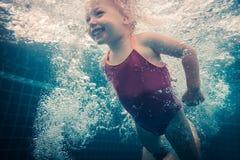 Lyckligt simma för barnlitet barn som är undervattens- i simbassäng fotografering för bildbyråer