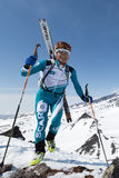 Lyckligt skidar bergsbestigaren som klättring till berget med skidar fastspänt för att vandra Royaltyfri Foto