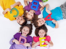 Lyckligt skola ungar med färgrikt alfabet märker Arkivfoton