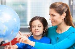 Lyckligt skolabegrepp Lärarinna som förklarar geografi till ungen royaltyfri foto