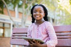Lyckligt skolflickasammanträde på bänk med den digitala minnestavlan Royaltyfri Foto