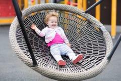 Lyckligt skratta behandla som ett barn flickan som kopplar av på en gunga Royaltyfri Foto
