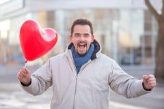 Lyckligt skratta den stiliga mannen med ett röd hjärta format luftballonanseende i en stadsgata royaltyfri foto