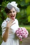 Lyckligt skratta för brud som täcker munnen med hennes hand med buketten av pionen, blommar Royaltyfri Foto