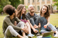 Lyckligt skratta parkerar studenter på gräs i universitet Royaltyfria Bilder