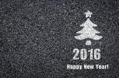 Lyckligt skriftliga nytt år och gran-träd på en bakgrund för asfaltväg Royaltyfri Foto