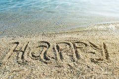 Lyckligt skriftligt för ord på stranden Arkivfoto