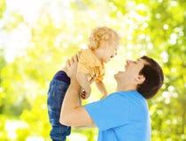 Lyckligt spela för faderbarn Farsan lyfter upp att le sonen över gräsplan Arkivfoto