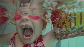 Lyckligt spela för ung flicka som är undervattens- i pöl arkivfilmer