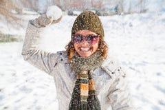Lyckligt spela för ung kvinna kastar snöboll kamp royaltyfria foton