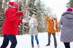Lyckligt spela för vänner kastar snöboll i vinterskog Royaltyfri Foto