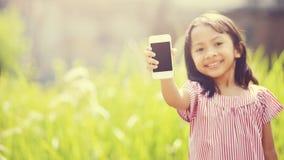 Lyckligt spela för flicka som är utomhus- med mobiltelefonen Royaltyfria Bilder