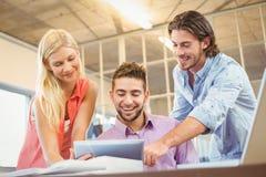 Lyckligt stilfullt affärsfolk som ser den digitala tabellen Fotografering för Bildbyråer